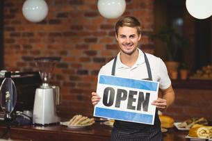Handsome waiter presenting open signの写真素材 [FYI00009673]