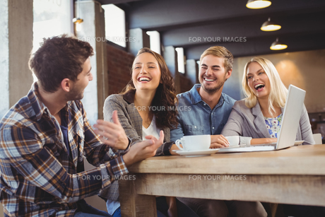 Smiling friends drinking coffee and laughingの写真素材 [FYI00009682]