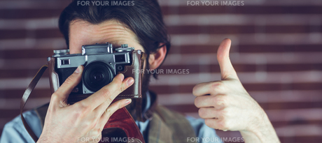 Man showing thumbs up gesture while photographingの素材 [FYI00009687]