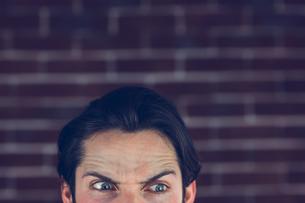 Angry man with raised eyebrows looking awayの素材 [FYI00009704]