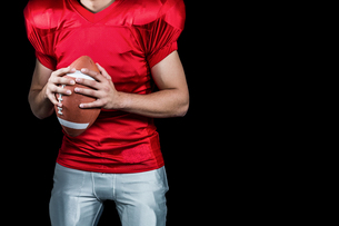 Mid section of American football player holding ballの素材 [FYI00009705]