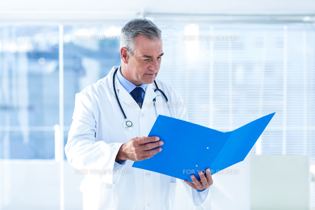 Male doctor reading document in hospitalの写真素材 [FYI00009716]