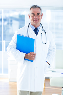 Portrait of male doctor with document in hospitalの写真素材 [FYI00009718]
