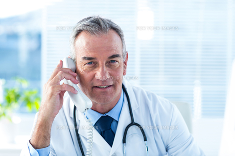 Male doctor talking on telephone in clinicの写真素材 [FYI00009723]