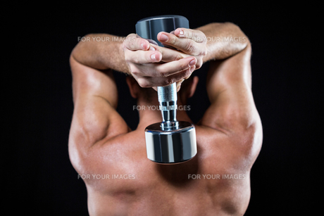 Rear view of shirtless sports player working out with dumbbellの写真素材 [FYI00009727]