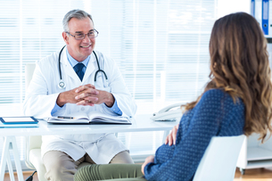Male doctor discussing with pregnant woman in clinicの写真素材 [FYI00009734]