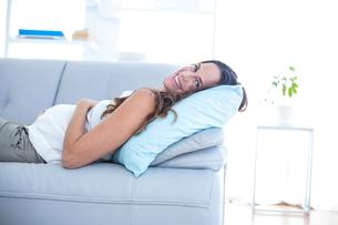 Happy pregnant woman lying on sofaの写真素材 [FYI00009737]