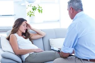 Thearapist advising pregenat woman on sofaの写真素材 [FYI00009744]