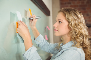 Beautiful woman holding sticky note while writing on glass boardの写真素材 [FYI00009748]
