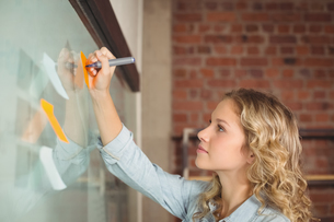 Creative businesswoman writing on sticky notes in officeの写真素材 [FYI00009760]