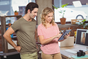 Woman showing digital tablet to colleague in officeの写真素材 [FYI00009799]