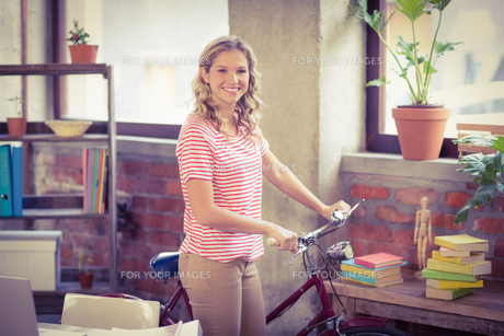 Businesswoman with bicycle standing in officeの写真素材 [FYI00009804]