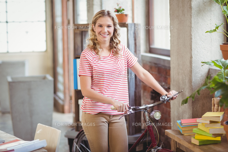 Portrait of businesswoman with bicycle in officeの写真素材 [FYI00009806]
