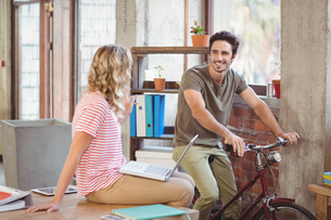 Man with bicycle discussing with colleague in officeの写真素材 [FYI00009822]