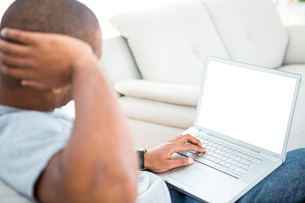 Man using laptop on sofaの写真素材 [FYI00009852]
