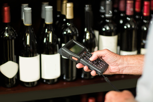 Senior man scanning wine bottlesの写真素材 [FYI00009903]