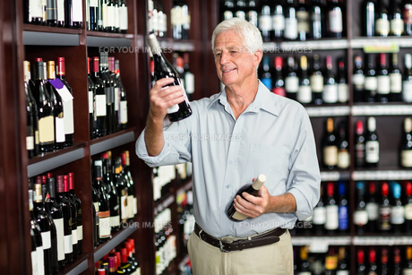 Smiling senior man choosing wineの写真素材 [FYI00009904]