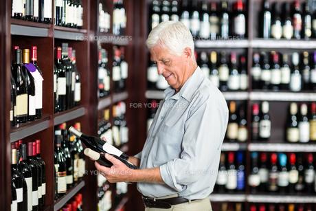 Smiling senior man choosing wineの写真素材 [FYI00009905]