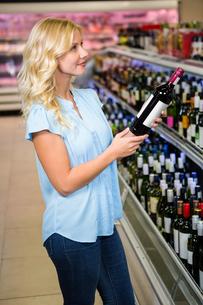 Blonde woman holding wine bottleの写真素材 [FYI00009910]