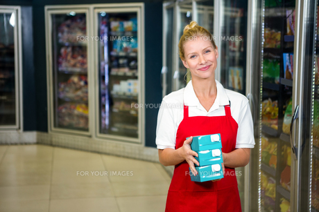 Smiling shop assistant holding productsの写真素材 [FYI00009928]