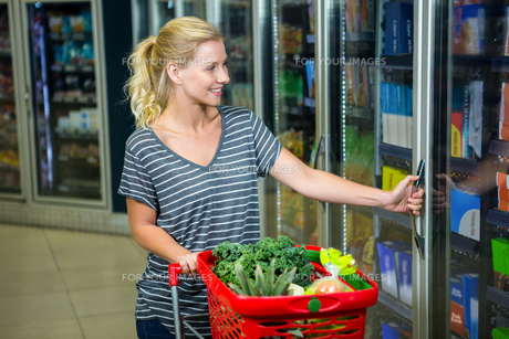 Smiling woman with shopping basket opening fridgeの写真素材 [FYI00009929]