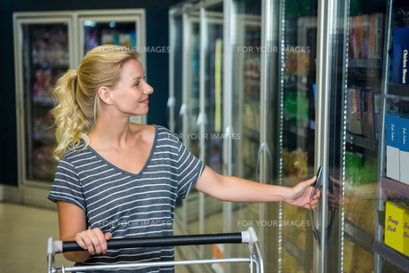 Smiling woman with cart opening fridgeの写真素材 [FYI00009937]