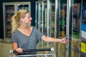 Smiling woman with cart opening fridgeの写真素材 [FYI00009937]