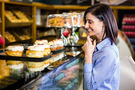 Pretty smiling woman choosing her dessertの写真素材 [FYI00009965]