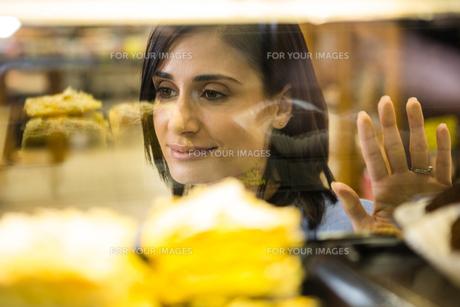 Pretty smiling woman choosing her dessertの写真素材 [FYI00009966]