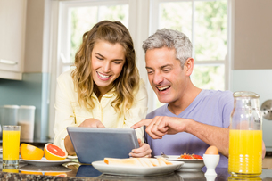Happy couple using tablet and having breakfastの写真素材 [FYI00010035]