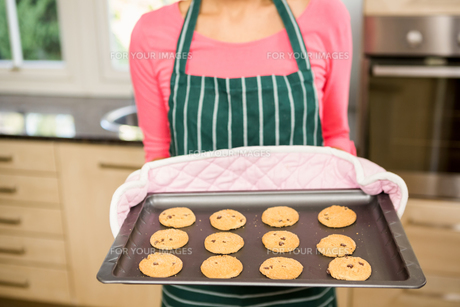 Mid section of woman showing biscuits on baking tinの写真素材 [FYI00010049]