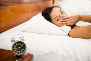 Brunette in the bed looking at alarm clock on the tableの写真素材 [FYI00010050]