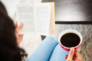 Cropped image of woman with coffee reading bookの写真素材 [FYI00010074]