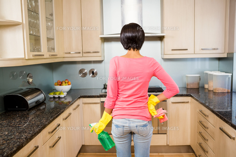 Rear view of standing brunette ready to clean the kitchenの素材 [FYI00010079]