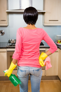 Rear view of standing brunette ready to clean the kitchenの素材 [FYI00010080]