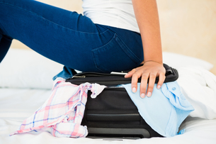 Woman sitting on her overfull suitcaseの写真素材 [FYI00010084]
