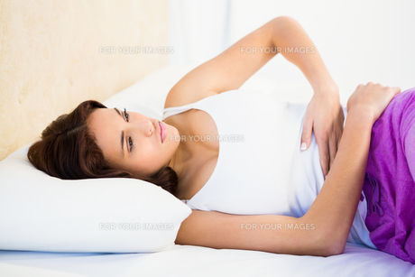 Woman lying on her bed with a belly painの写真素材 [FYI00010087]
