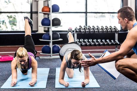 Fitness class doing exercises on matの写真素材 [FYI00010100]