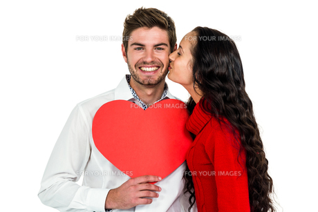 Man holding paper heart and being kissed by girlfriendの写真素材 [FYI00010107]