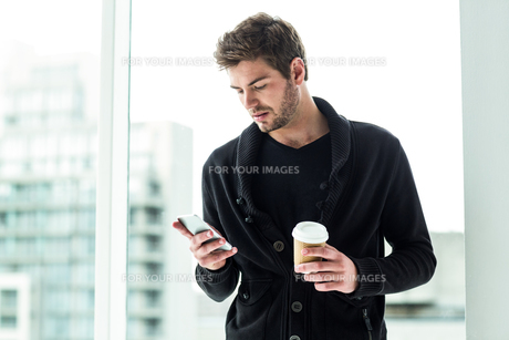 Handsome man using smartphone and holding disposable cupの素材 [FYI00010129]