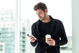 Handsome man using smartphone and holding disposable cupの写真素材 [FYI00010129]