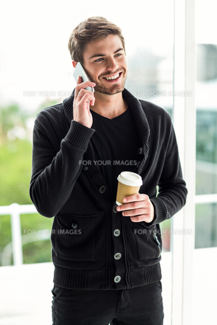 Handsome man on phone call holding disposable cupの素材 [FYI00010142]