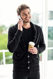 Handsome man on phone call holding disposable cupの写真素材 [FYI00010142]