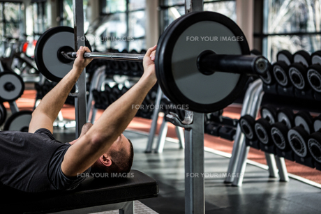 Muscular man lifting barebell while lying on benchの写真素材 [FYI00010152]