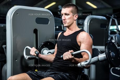Serious muscular man using exercise machineの写真素材 [FYI00010154]