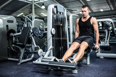Muscular man using exercise machine for legsの写真素材 [FYI00010158]