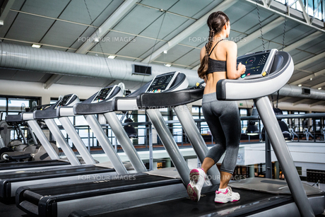 Rear view of woman jogging in treadmillの写真素材 [FYI00010175]