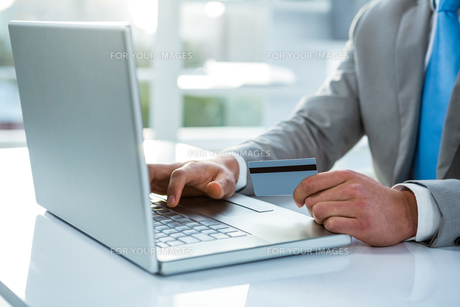 Businessman holding his credit card to payの写真素材 [FYI00010184]