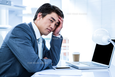Tired businessman holding his headの写真素材 [FYI00010188]