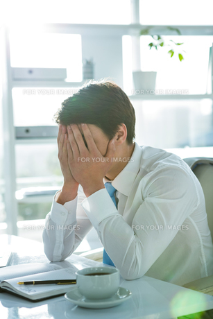 Tired asian businessman working at his deskの写真素材 [FYI00010201]